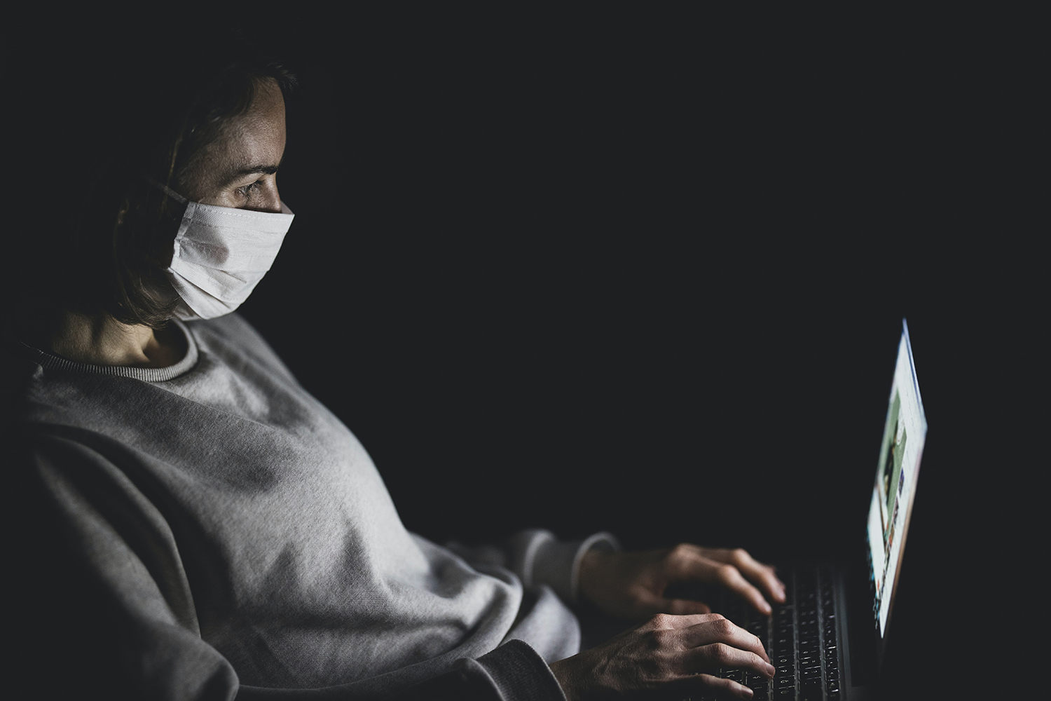 person wearing a face mask looking at their laptop