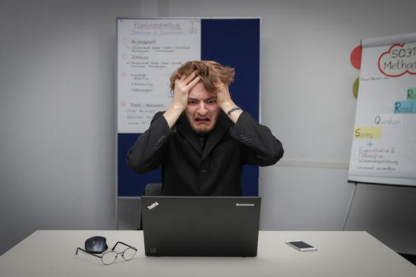 Stressed man sitting at computer pulling his hair