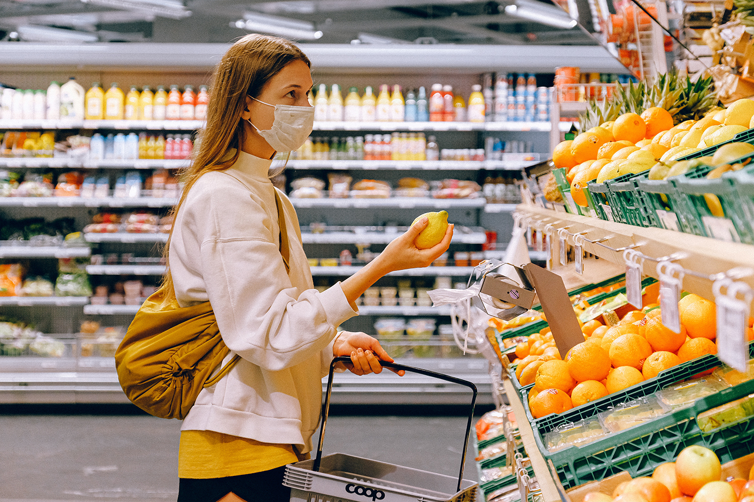 Woman wearing face mask holding a lemon at a grocery store